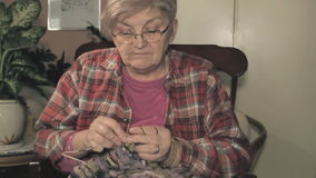 Elderly woman knitting stock footage