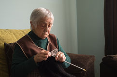 Elderly woman knitting at home. Stock Photos