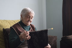Elderly woman knitting at home Royalty Free Stock Images