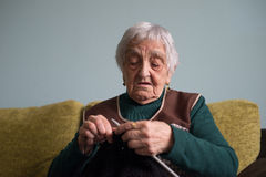 Elderly woman knitting at home Stock Images