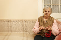 Elderly woman knitting with red wool Royalty Free Stock Photo
