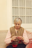 Elderly woman knitting with red wool Royalty Free Stock Images