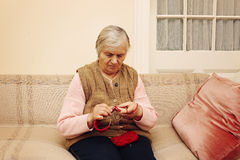 Elderly woman knitting with red wool Stock Images
