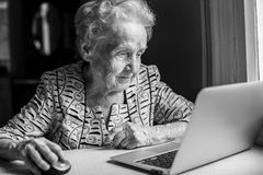 An elderly woman with a laptop. Black-and-white photo Royalty Free Stock Image