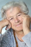 Elderly woman leaning on hands Stock Image