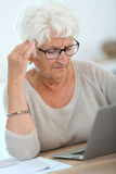Elderly woman learning how to use laptop Stock Photos