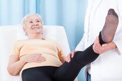 Elderly woman during leg rehabilitation Stock Photos