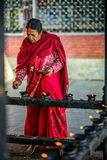 Elderly woman  lighting candles before prayer in Kathmandu, Nepa Royalty Free Stock Photo