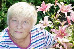 Elderly woman and lily Stock Photos