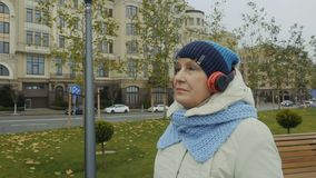 Elderly woman listen music with headphones walking in the city. Grandmother wearing warm clothes walks at the urban street in headphones. Camera moves around the stock footage
