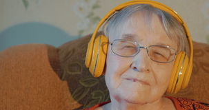 Elderly woman listening to music in headphones stock video footage