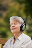 Elderly woman listening to some music Stock Image