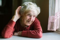 An elderly woman listens with her hand to her ear. stock image