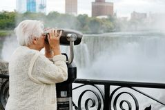 Elderly woman looking at american falls in niagara. Beautiful elderly woman looking at american falls in niagara royalty free stock photos