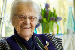 Elderly woman looking at the camera and smiling Stock Photography