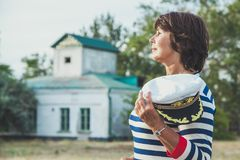 Elderly woman looking into the distance on seashore. Pretty pleased elderly woman in striped dress and marine cap on the beach put her hand to visor at Stock Image