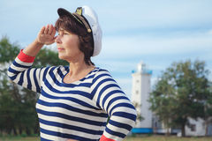 Elderly woman looking into the distance on seashore Stock Image