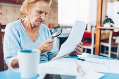 Elderly woman looking at her utility bills Royalty Free Stock Image