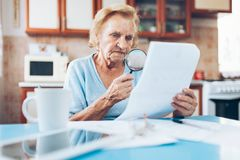 Elderly woman looking at her utility bills Stock Image