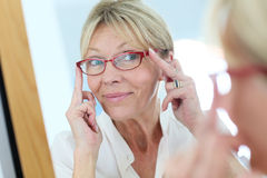 Elderly woman looking in the mirror trying on eyeglasses Royalty Free Stock Image