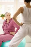 Elderly woman looking at personal trainer. Elderly woman sitting on fit ball looking at personal trainer demonstrating exercise stock photography
