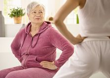 Elderly woman looking at personal trainer. Elderly women looking at personal trainer demonstrating exercise royalty free stock images