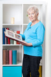 Elderly woman looking through photo album Stock Image