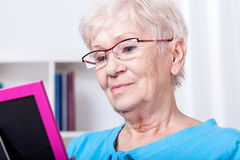Elderly woman looking at photography Stock Images
