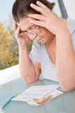 Elderly woman looking at a receipt for payment of utilities. Royalty Free Stock Image