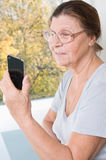 Elderly woman looking at the screen of mobile phone and smiling. Studio photography at the table on a light background Stock Photography