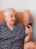 Elderly woman looking at a smartphone Stock Images