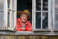 Elderly woman looking from the window of the farmhouse. Fun. Royalty Free Stock Image