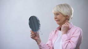 Elderly woman looking at wrinkled face in mirror, thinking about plastic surgery stock video