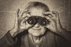 Elderly woman looks through binoculars. Stock Photos