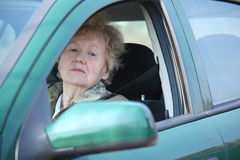 Elderly woman looks in car`s window Stock Photography