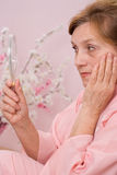 Elderly woman looks in the mirror Royalty Free Stock Image