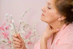 Elderly woman looks in the mirror Stock Photos