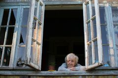 An elderly woman looks out of the window. Royalty Free Stock Photos