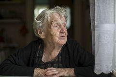 Elderly woman looks out the window. Expression. Stock Photography