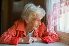 An elderly woman looks out the window. Royalty Free Stock Image