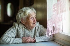 An elderly woman looks out the window sitting in his house. Care of lonely pensioners stock image