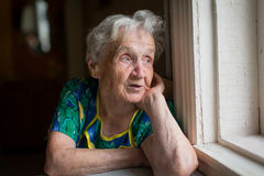 Elderly woman looks out the window sitting in the kitchen. Stock Photo