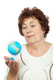 Elderly woman looks at small globe Stock Photos