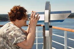 Elderly woman looks through telescope on landscape Stock Photo