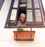 Elderly woman looks through window Royalty Free Stock Photography