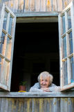 Elderly woman looks from window of a village house. Royalty Free Stock Photos