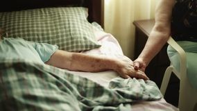 Elderly Woman lying down and holding another woman's hands. Two Unrecognizable Women holding Hands while the elderly one is lying down in bed and the other one stock footage