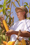 Elderly woman with maize Royalty Free Stock Image