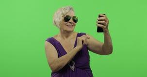 An elderly woman make a photo on a smartphone. Selfie. Chroma key. An elderly woman make a photo on a smartphone. Selfie. Old pretty grandmother in a purple stock video
