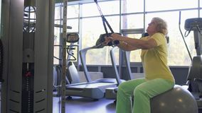 Elderly woman makes pull up exercise on training apparatus in the gym. Granny trains her arms sitting on fitness ball. Senior woman has a healthy lifestyle and stock footage